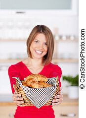 Woman holding a basket of fresh croissants