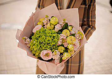 Woman holding a beautiful bouquet of flowers wrapped in craft paper on autumn day