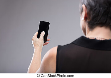 Woman holding a blank black mobile phone