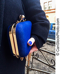 Woman holding a blue handbag in her hand