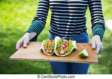 Woman holding a board with Mexican tacos. Closeup.