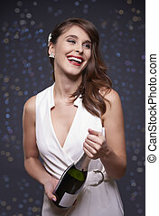Woman holding a bottle of champagne