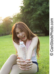 Woman holding a bottle of water and handed it to.
