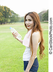 Woman holding a bottle of water.