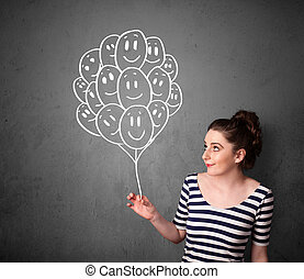 Woman holding a bunch of smiling balloons