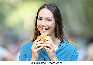 Woman holding a burger looking at camera