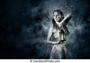 Beautiful young woman in white long dress holding a candle lantern