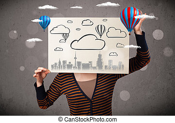 Woman holding a cardboard with cityscape in front of her head