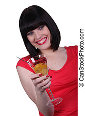 Woman holding a champagne glass full of fruit salad