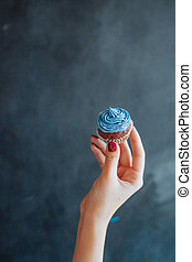 Woman holding a chocolate muffin on black background.