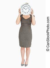 Woman holding a clock hiding her head