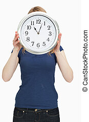 Woman holding a clock in front of her face