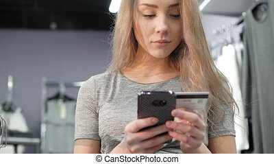 Woman holding a credit card and using mobile phone for online shopping. 4K