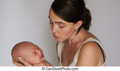 Woman holding a crying baby while hugs him