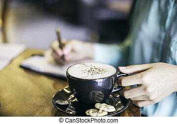 woman holding a cup of cappuccino