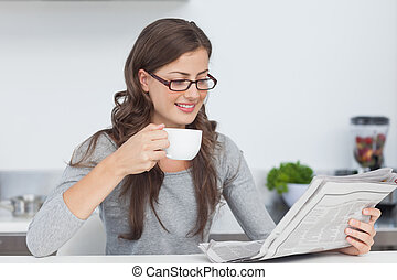Woman holding a cup of coffee and reading a newspaper