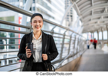 woman holding a cup of coffee in city