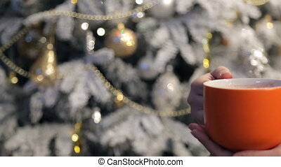 Woman holding a cup of orange at the Christmas tree.
