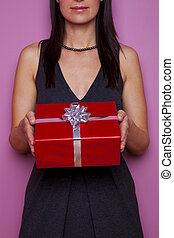 Woman holding a gift wrapped in red paper