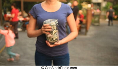 Woman holding a glass jar with dollars on a city street background