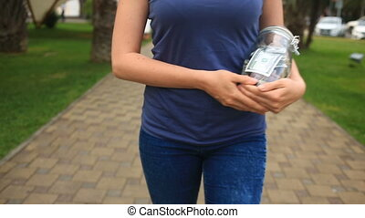 Woman holding a glass jar with dollars on a city street...
