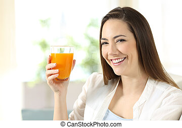 Woman holding a glass of orange juice looking at you