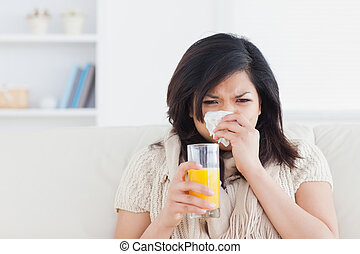 Woman holding a glass of orange juice while sneezing