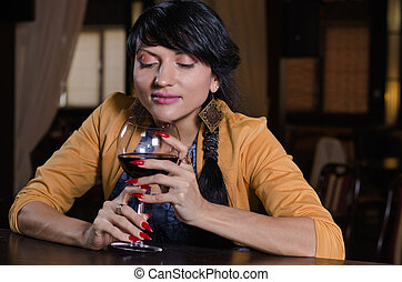 Woman holding a glass of red wine at the bar