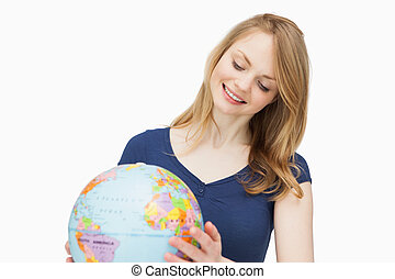 Woman holding a globe while smiling