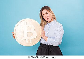 woman holding a Golden Bitcoin. virtual money.