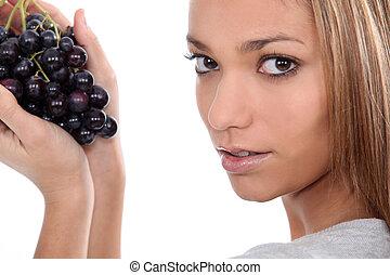 woman holding a grape