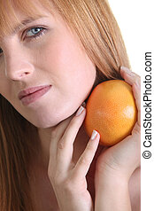Woman holding a grapefruit