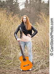 Woman holding a guitar outdoors, travel concept