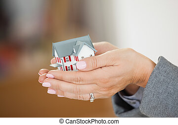 Woman holding a house in her hands