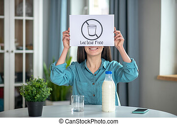 Woman holding a lactose free sign while drinking milk
