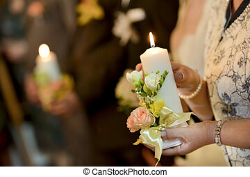 Woman holding a lighted candle in church