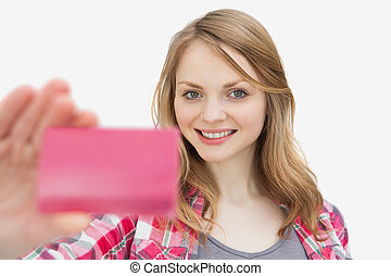 Woman holding a loyalty card while looking at camera