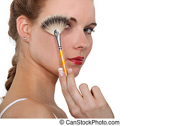 Woman holding a make-up brush in front of her face