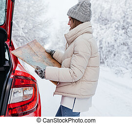 Woman holding a map in her hands while searching for a route on the side of the road in winter forest