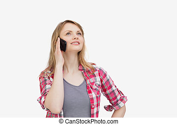 Woman holding a mobile phone while looking up