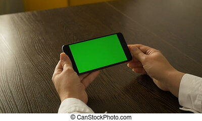Woman holding a mobile phone with a green screen. For your video content.