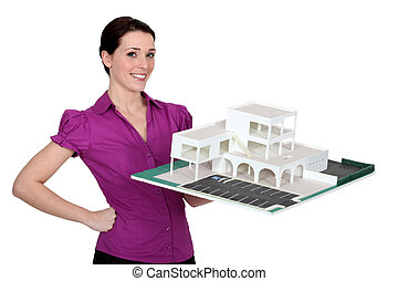 woman holding a model of a building