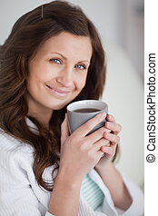 Woman holding a mug of coffee while looking at camera