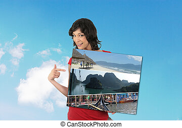 Woman holding a painting with the sky as background.