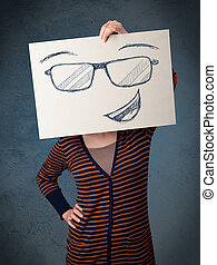 Woman holding a paper with smiley face in front of her head...