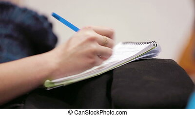Woman holding a pen and notebook.