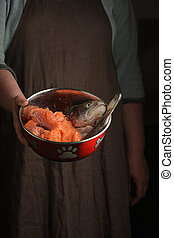 Woman holding a pet bowl with raw trout in hand. Rustic style.