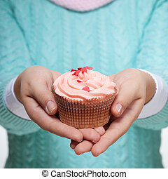 Woman holding a pink cupcake on white