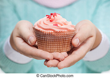 Woman holding a pink cupcake on white - Young woman holding...