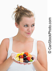 Woman holding a plate of fruit